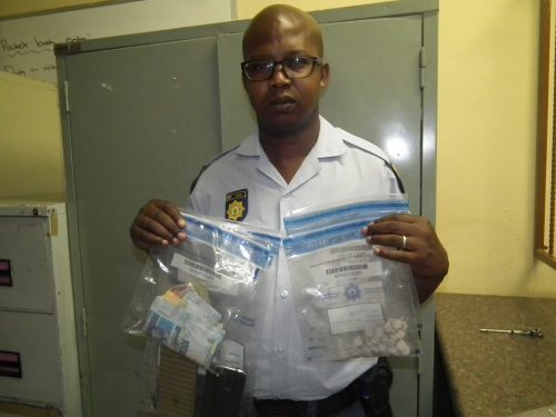Constable Thapelo Lethube showing confiscated drugs and cash. Photo: Supplied.
