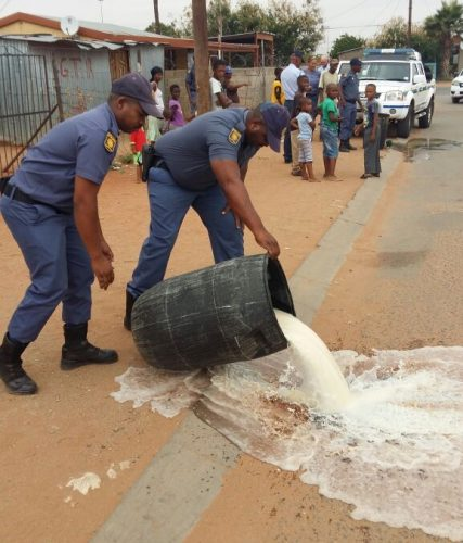 Cst Mc Collin Nkosi , Cst Lungephi Mira destroying home distilled beer. Photo: Supplied.